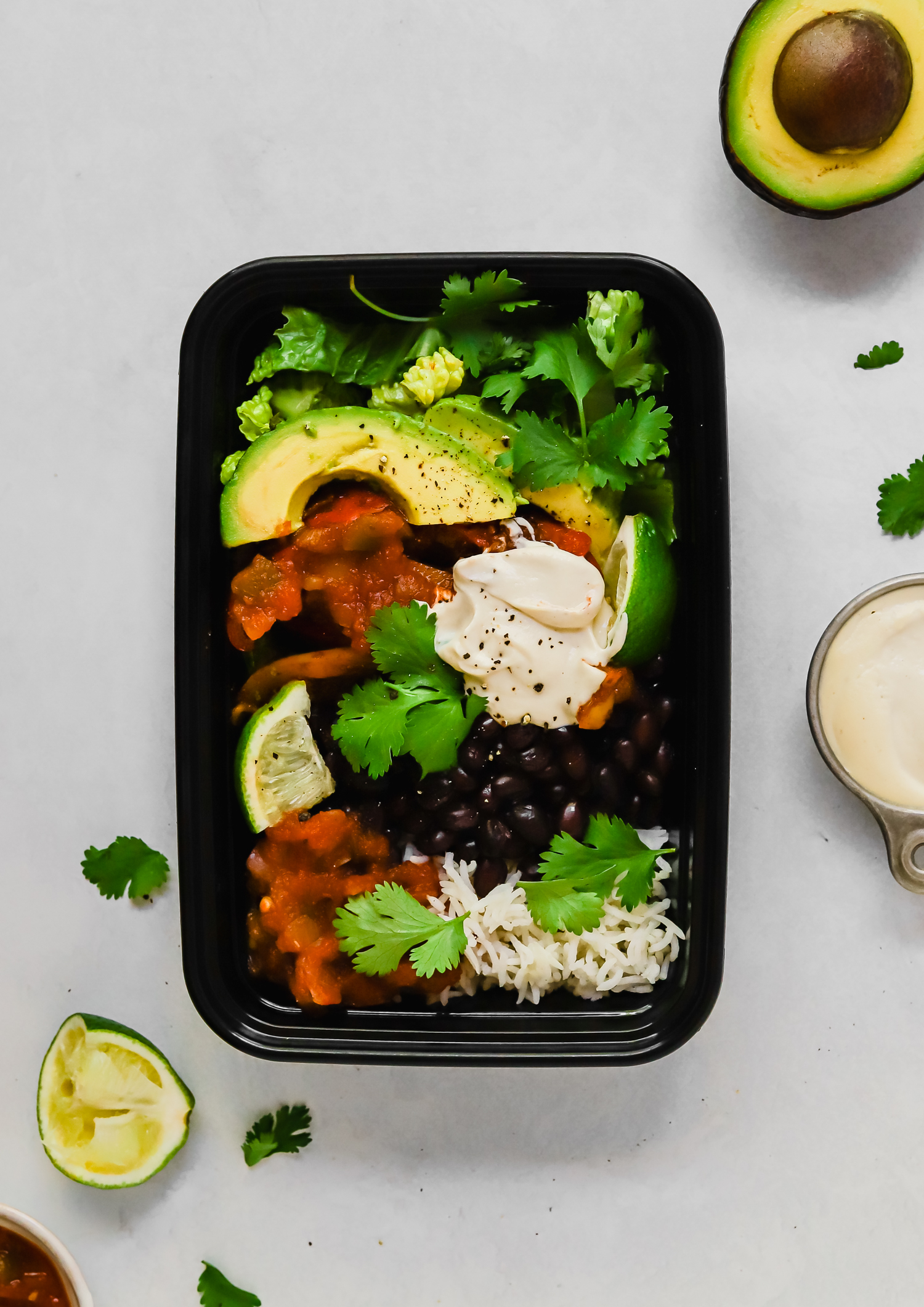 Vegan burrito bowl in a black meal prep container surrounded by lime wedges, vegan sour cream, and cilantro.