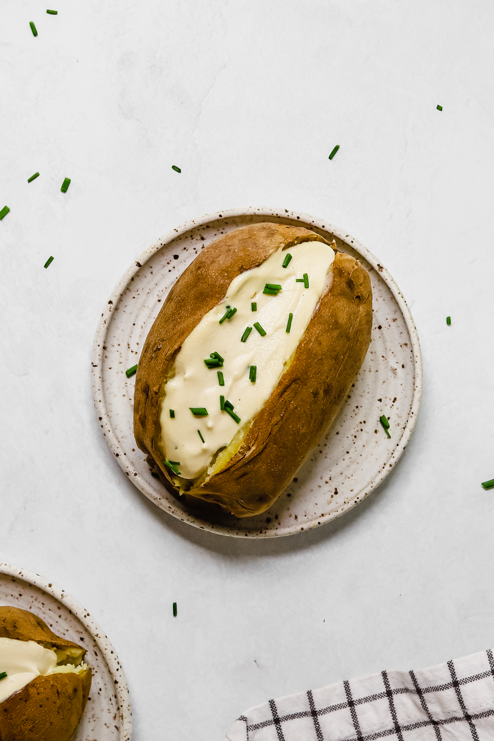 Baked potato on a small plate, cut in half and topped with cashew sour cream and chopped chives.