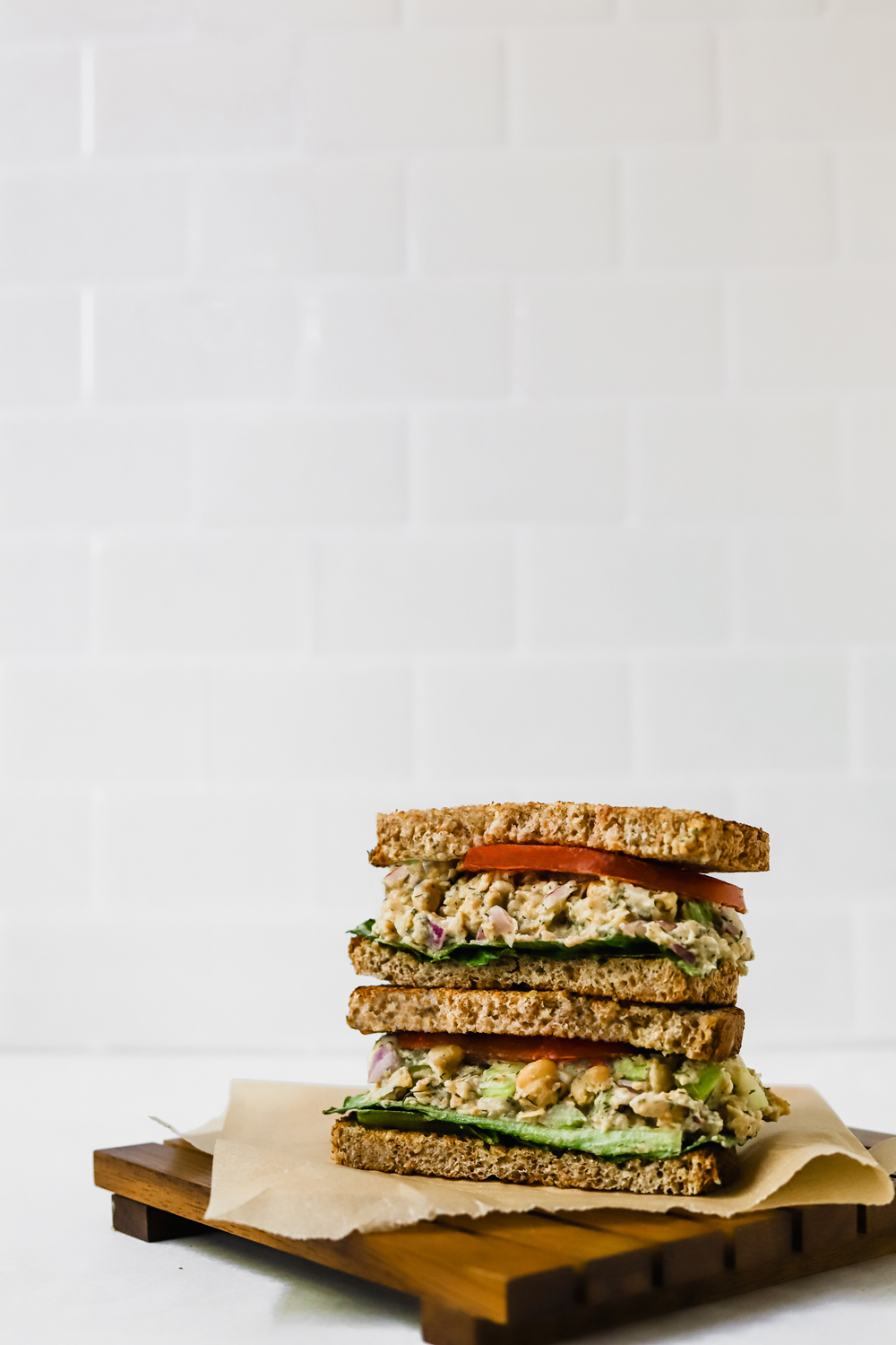 Vegan chickpea salad sandwich cut in half and stacked.