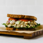 Chickpea salad sandwich with lettuce and tomato on wheat bread.