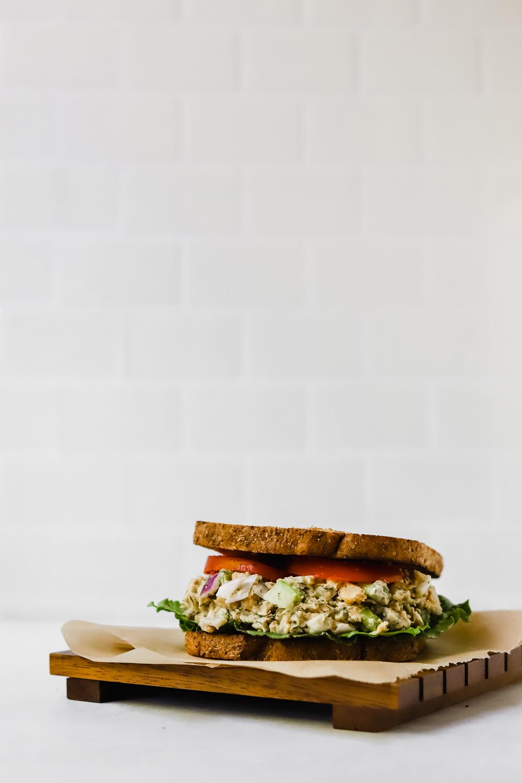 Vegan chickpea salad sandwich on brown parchment paper.