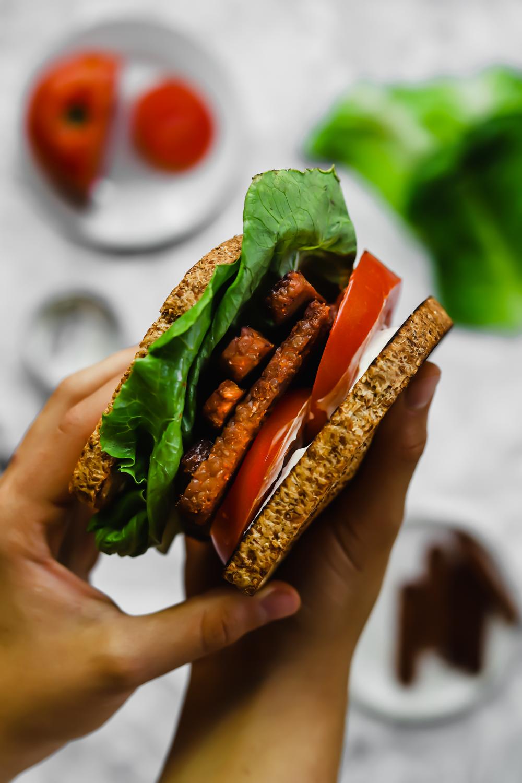 Hands holding a vegan BLT sandwich.