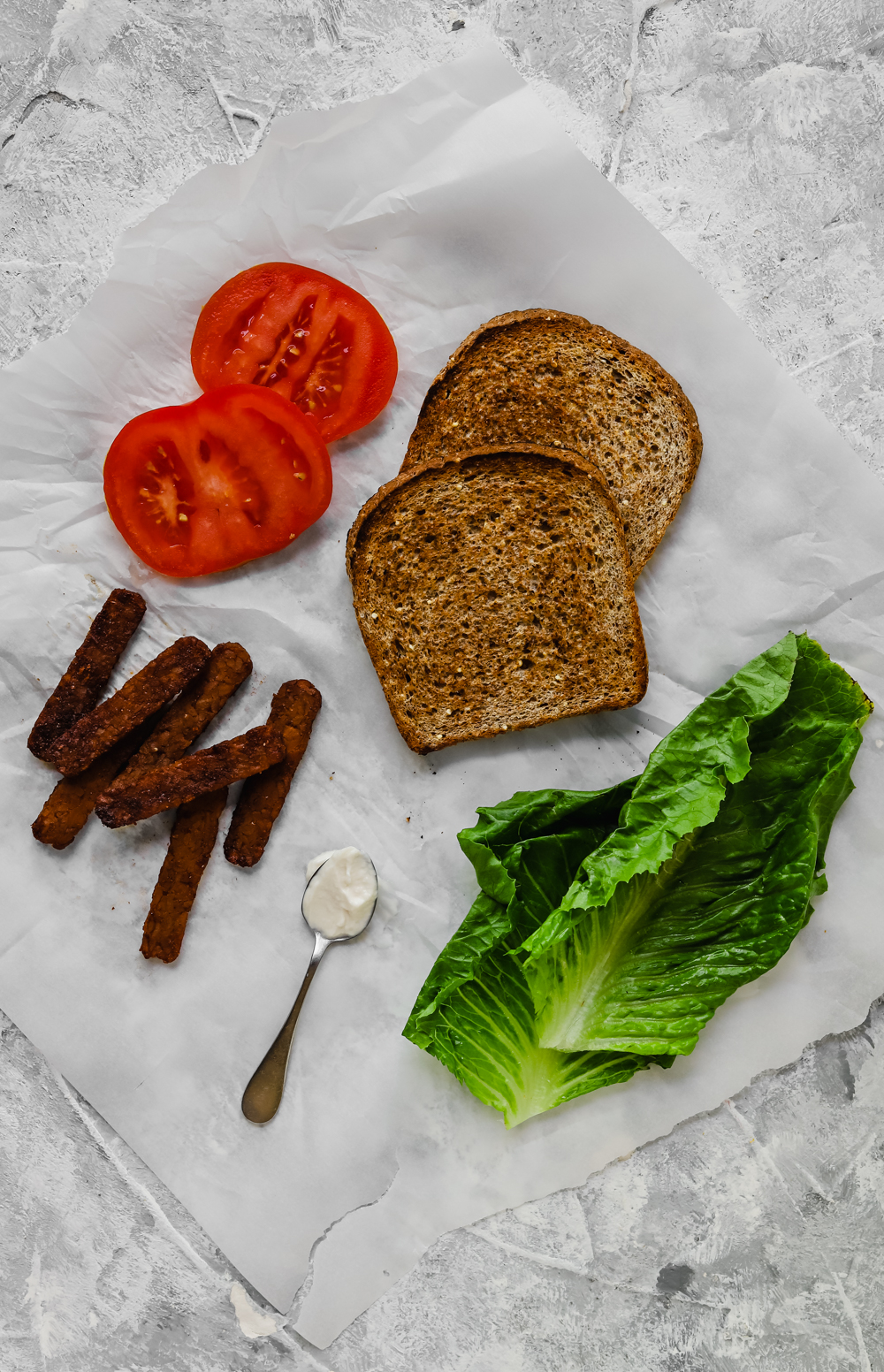 Ingredients for a vegan BLT with tempeh bacon on a piece of parchment paper.