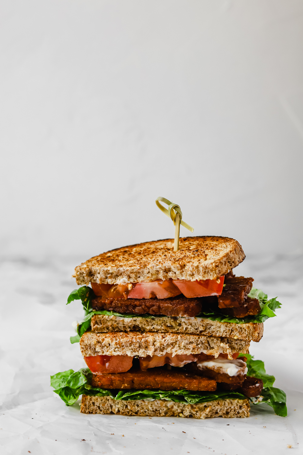 Vegan BLT sandwich cut in half and stacked.