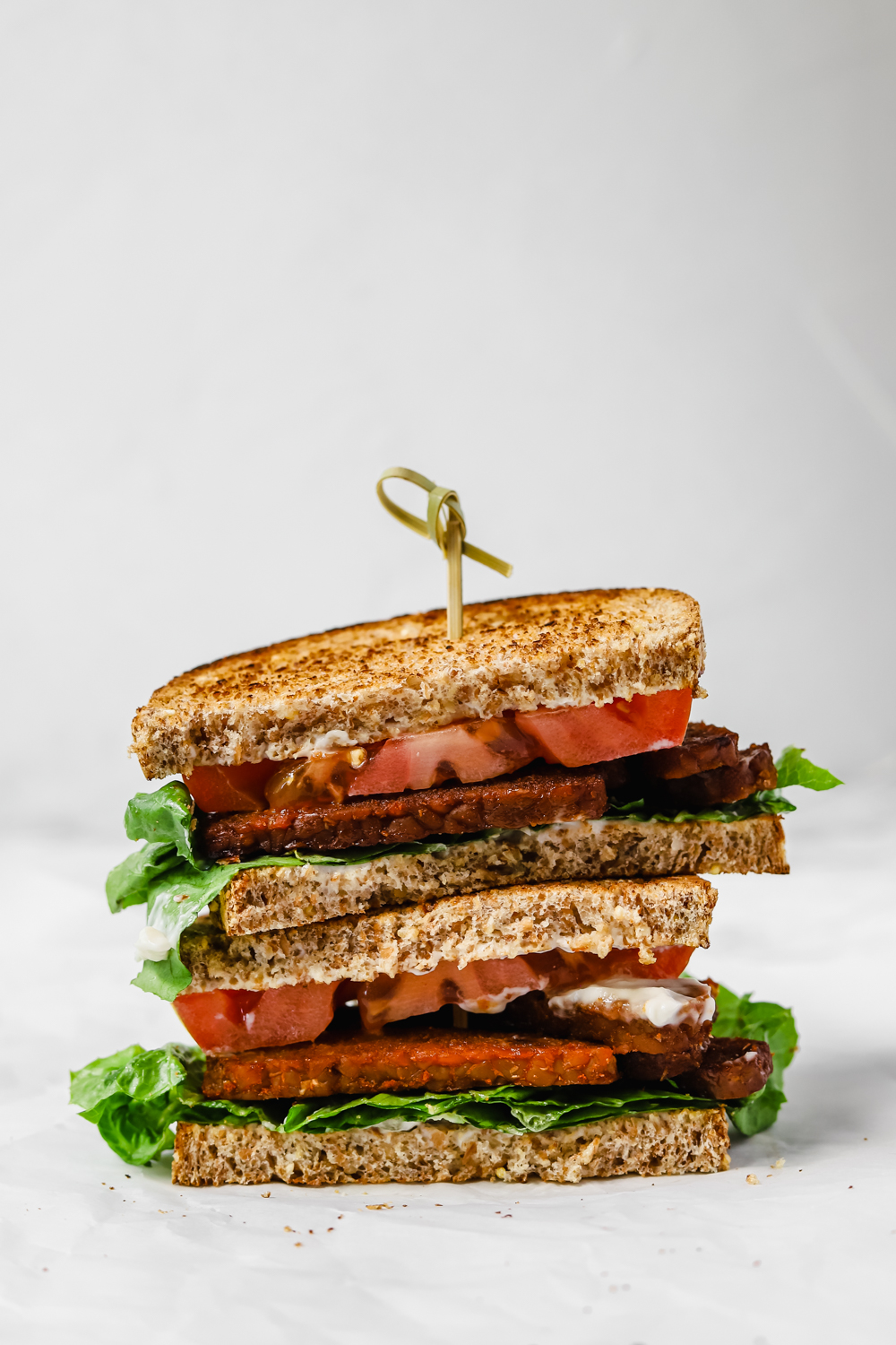 Vegan BLT sandwich with tempeh bacon cut in half.