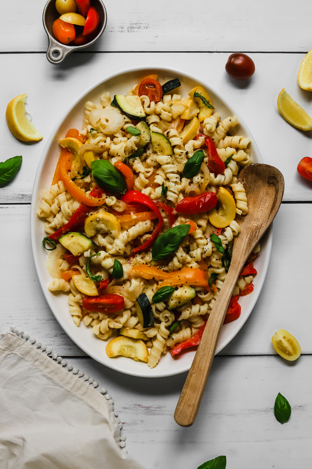 Large white platter of creamy vegan pasta with zucchini, tomato, onion, yellow squash, and red bell peppers.
