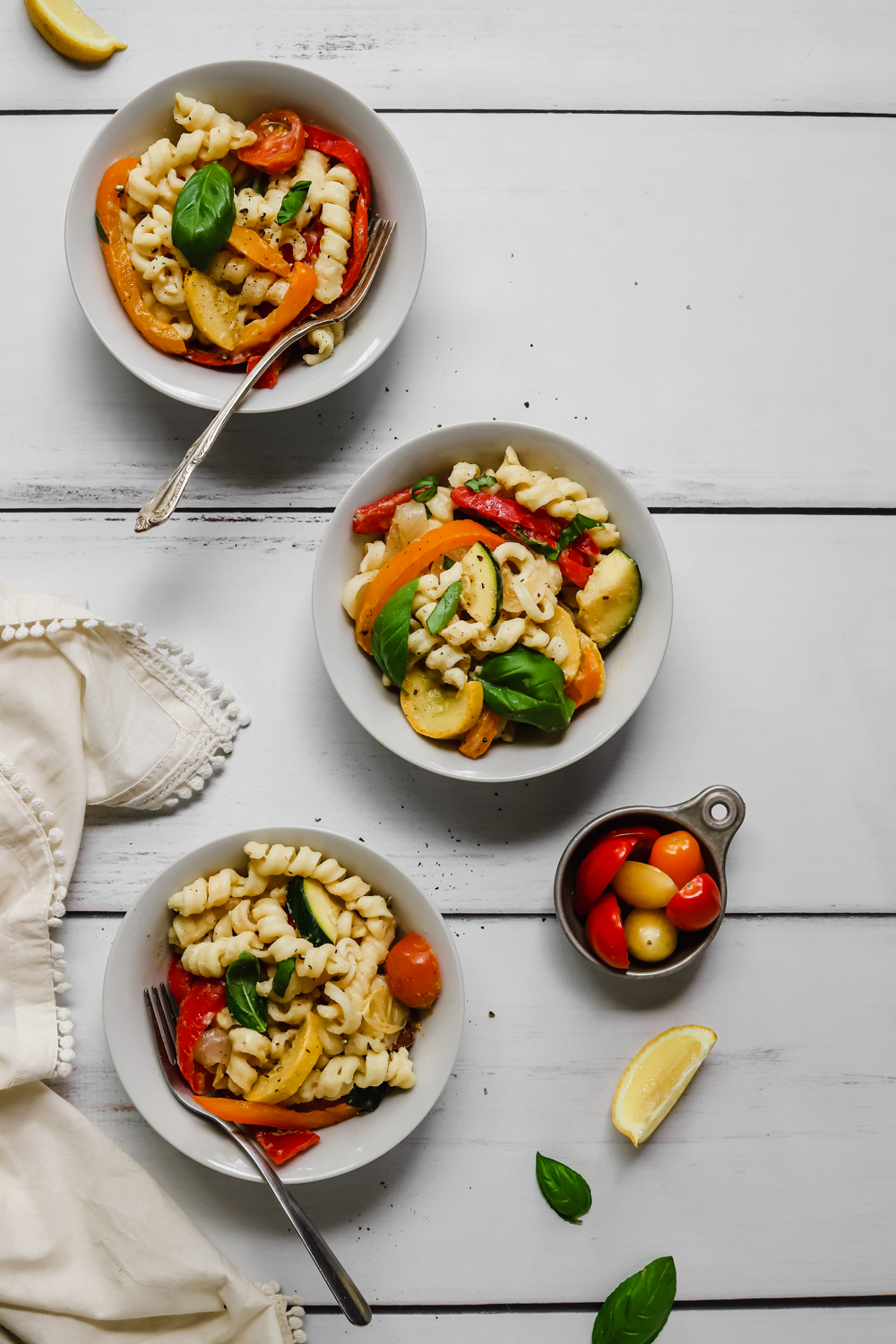 Three small white bowls of creamy pasta with veggies on a white wooden table.