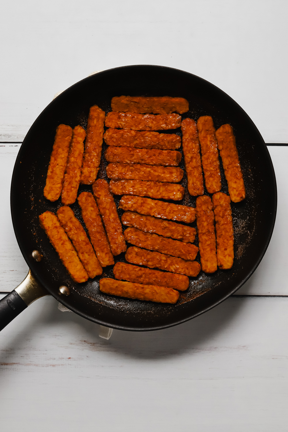 Pieces of marinated tempeh in a large black skillet.