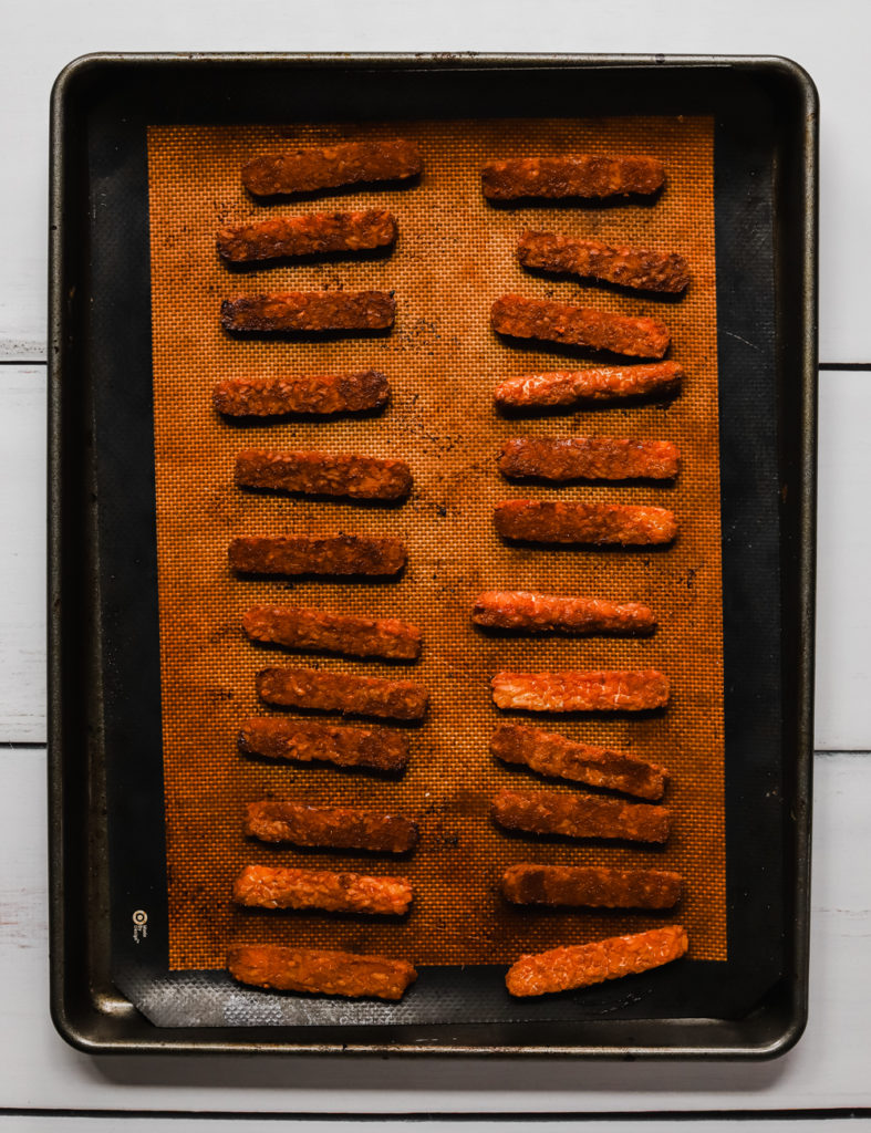Crispy baked tempeh slices on a baking tray lined with a reusable silicone mat.