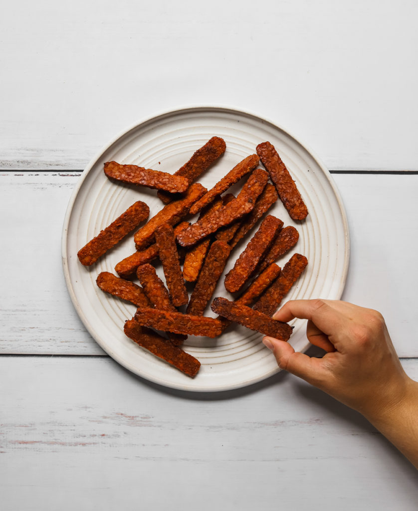Hand grabbing a piece of tempeh bacon off a large white platter.