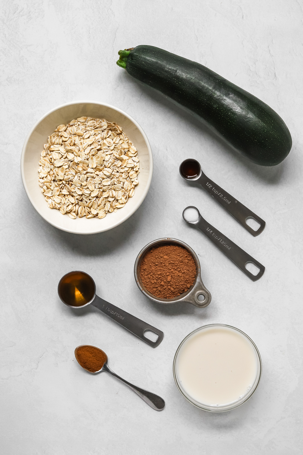 Ingredients to make vegan chocolate zucchini oatmeal: oats, zucchini, vanilla, maple syrup, salt, cinnamon, almond milk.