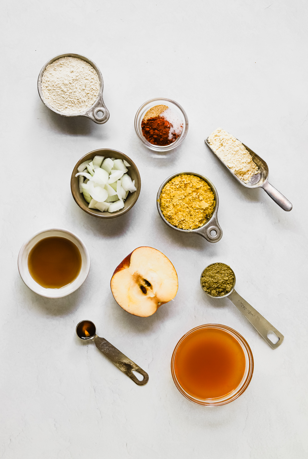 Ingredients to make seitan sausage: vital wheat gluten, chickpea flour, nutritional yeast, vegetable broth, liquid smoke, maple syrup, onions, sage, and spices.
