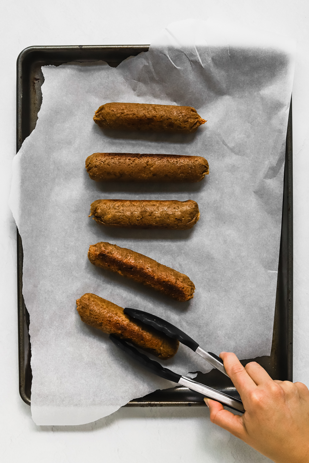 Grabbing a cooked seitan sausage off a baking tray with tongs.