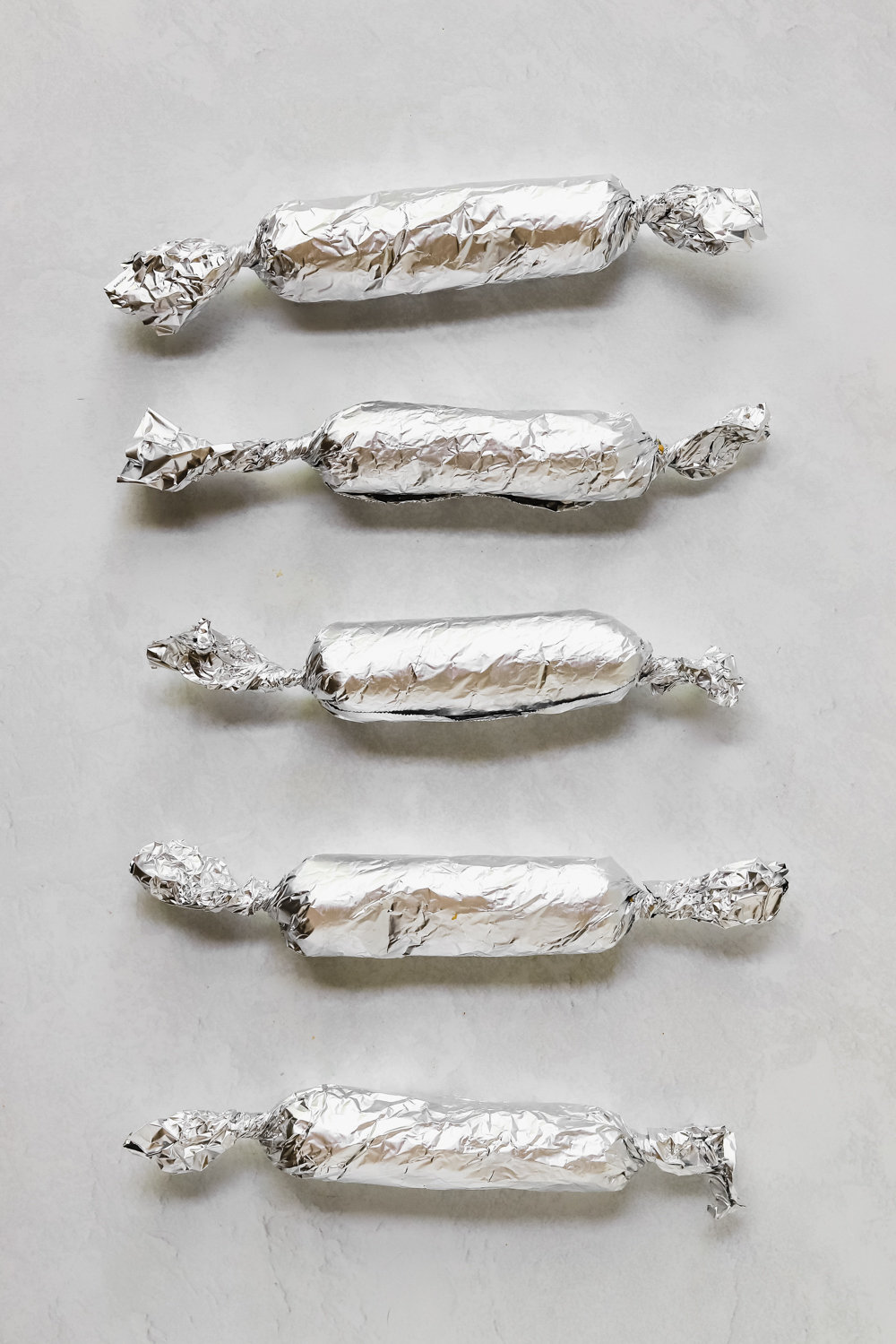 Uncooked seitan sausage dough wrapped up in aluminum foil before baking.
