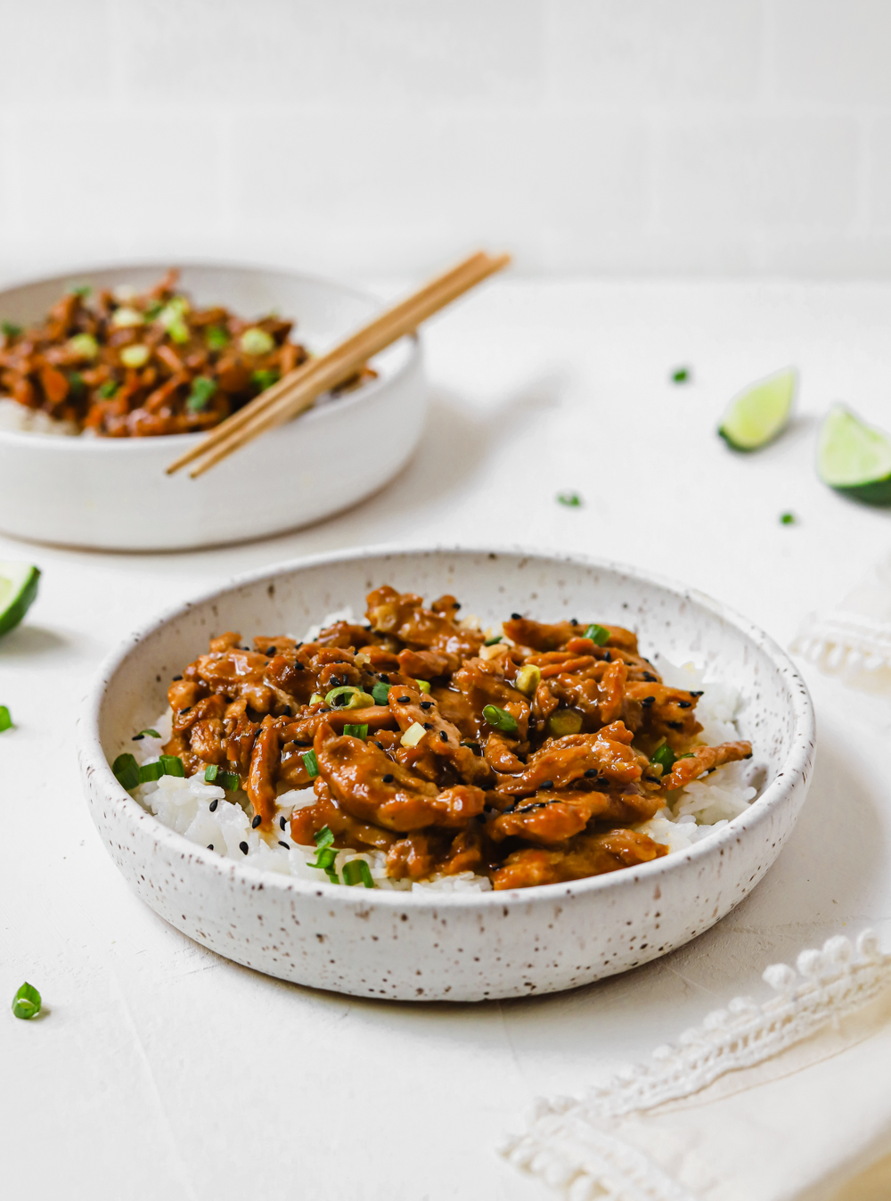 Bowl of vegan teriyaki soy curls topped with black sesame seeds and chopped green onions.