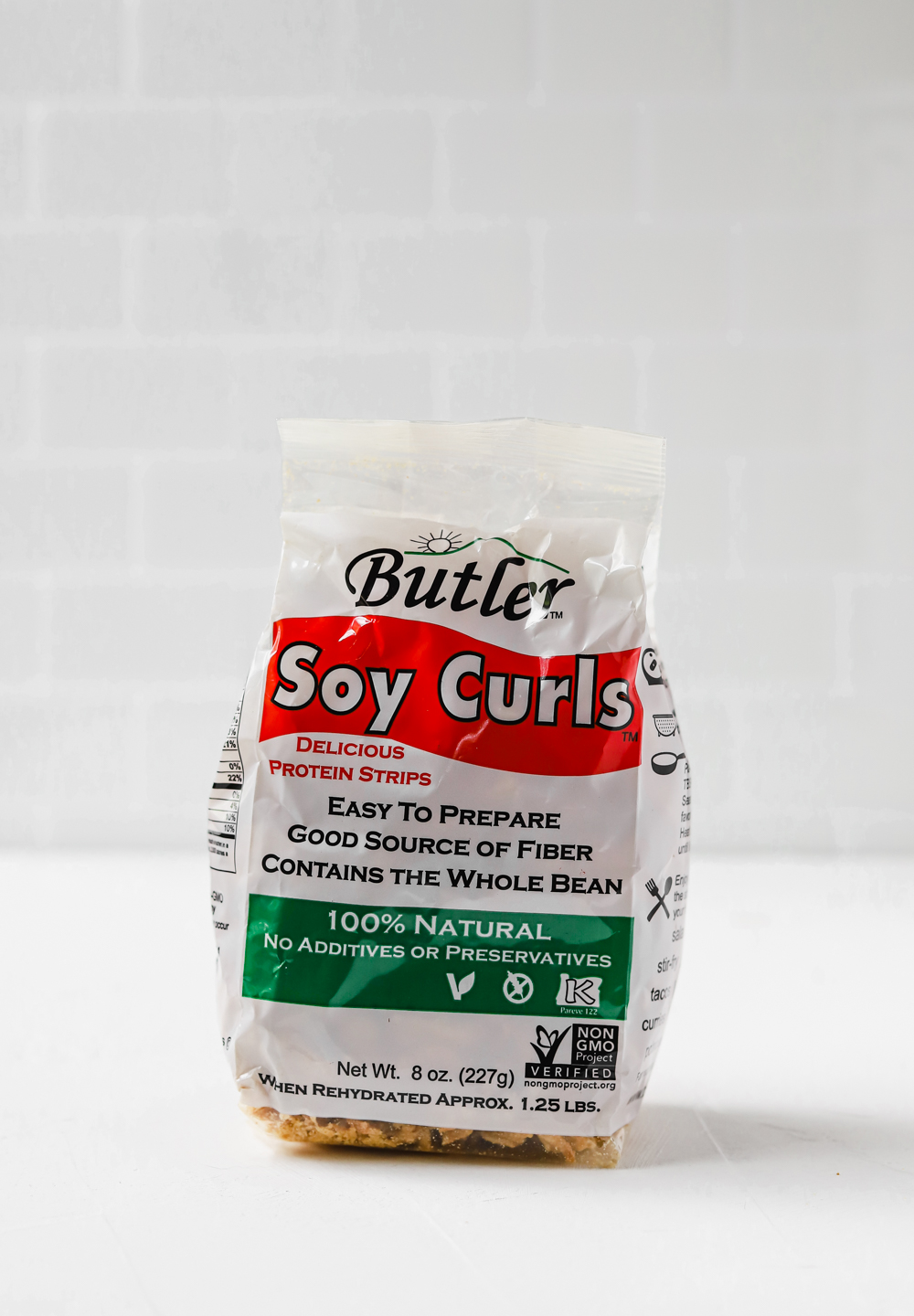 A bag of Butler Food's soy curls on a white countertop.