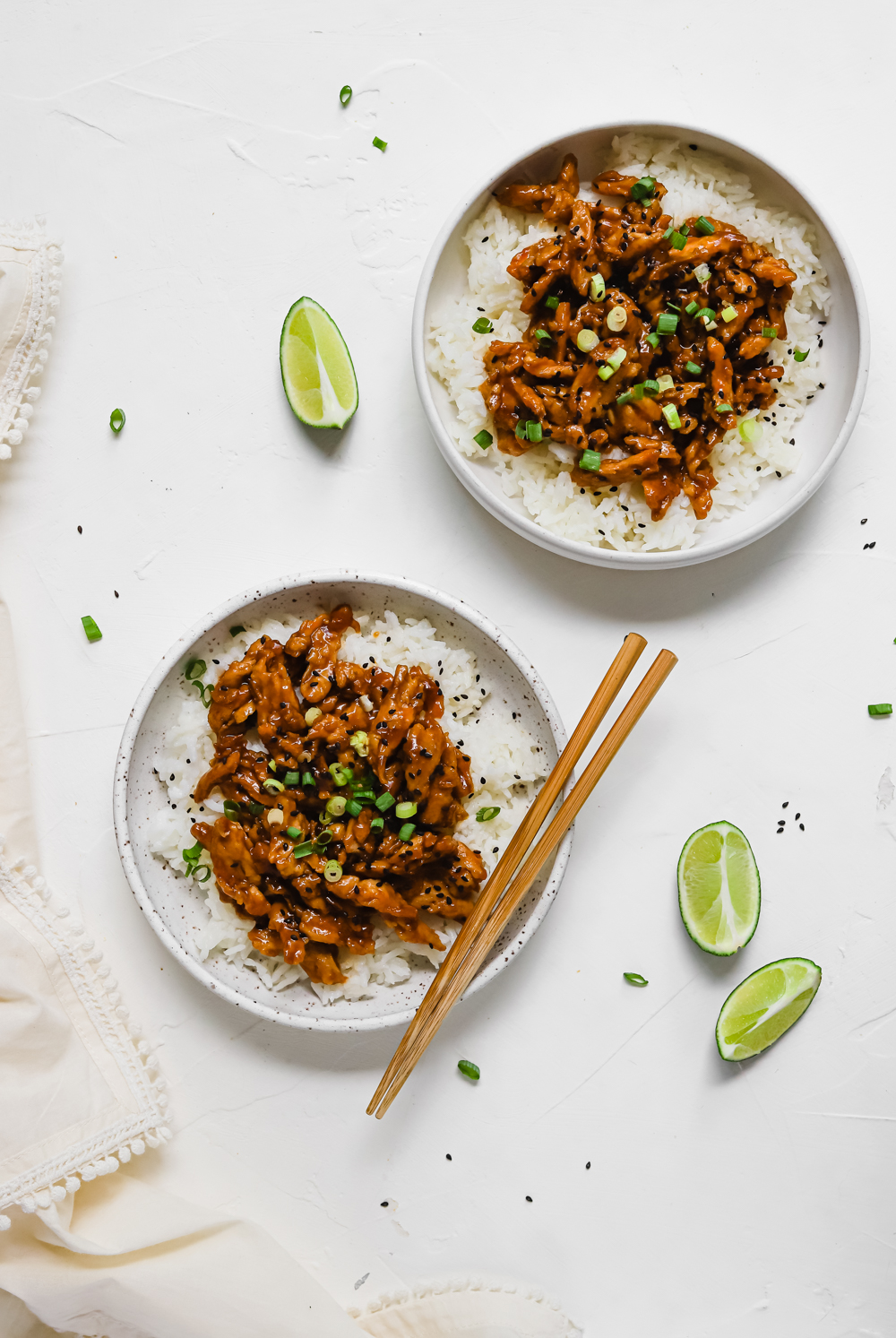 Two big bowls of teriyaki soy curls on a bed of rice.
