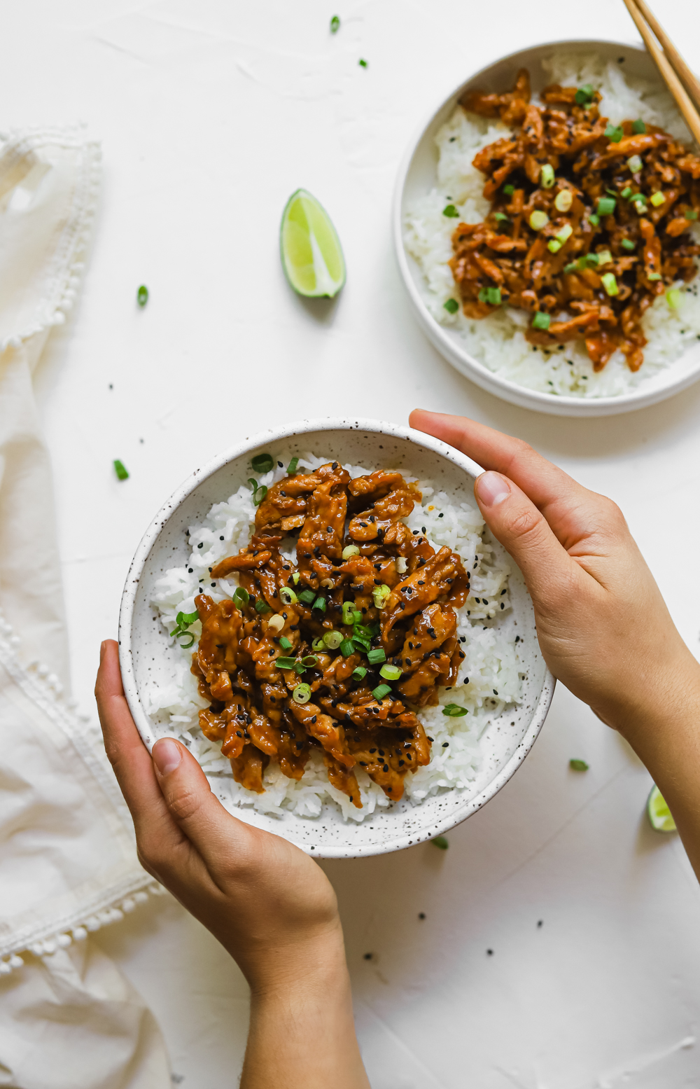 Hangs holding a bowl of vegan teriyaki soy curls on a bed of rice and topped with black sesame seeds and scallions.