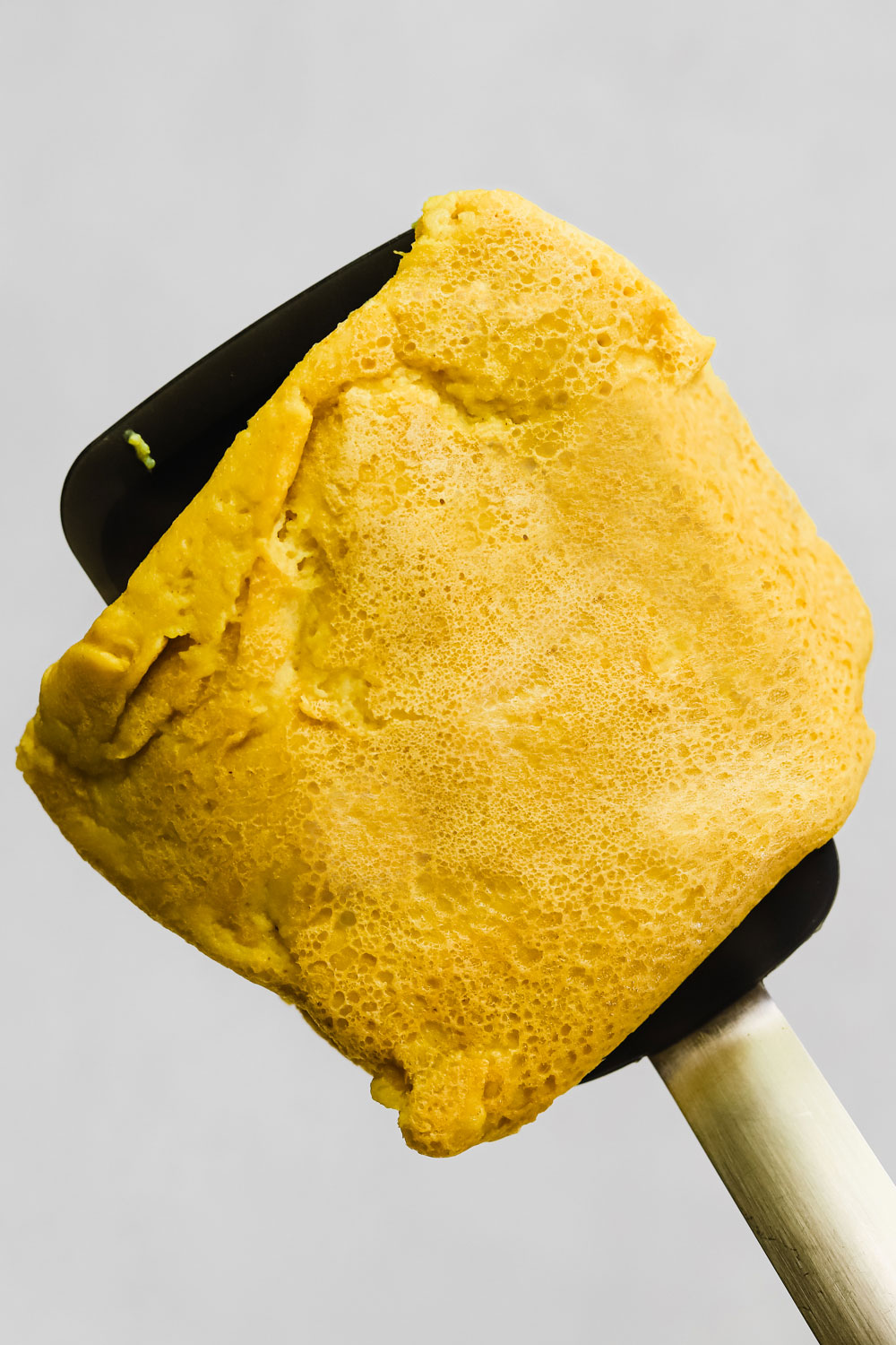 Very realistic vegan egg on a spatula.