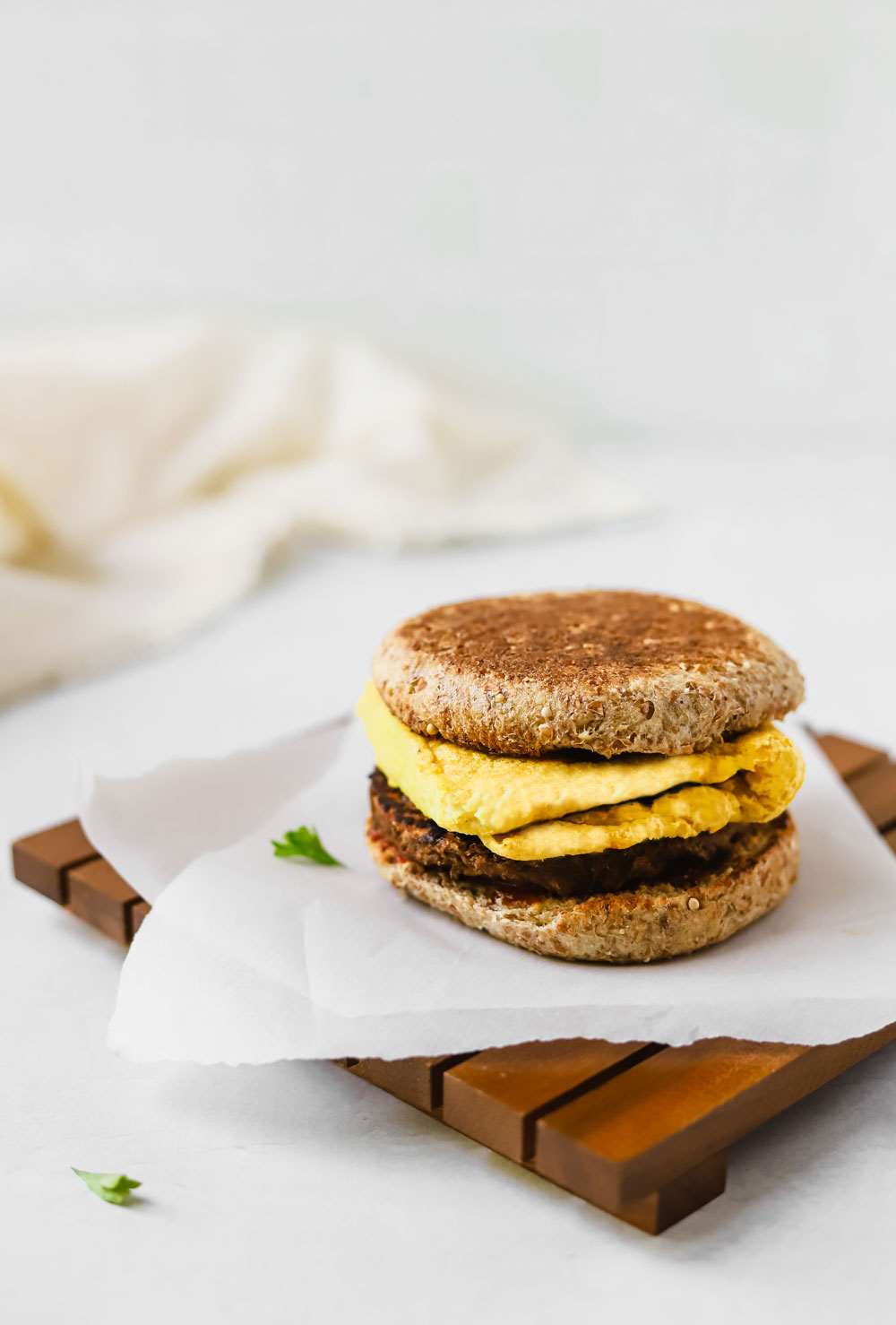 Delicious breakfast sandwich with vegan egg, vegan sausage patty, and toasted english muffin on a piece of white parchment paper.