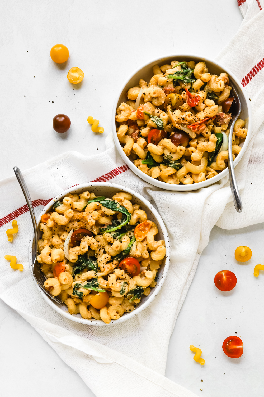 Two big bowls of hummus pasta with veggies.