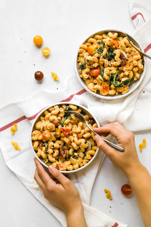 Digging into a big bowl of vegan hummus pasta.