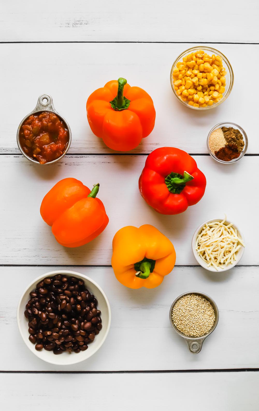 Ingredients to make vegan stuffed bell pepper jack o'lanterns: bell peppers, salsa, corn, black beans, quinoa, vegan mozzarella cheese, cumin, chili powder, garlic powder, and salt.