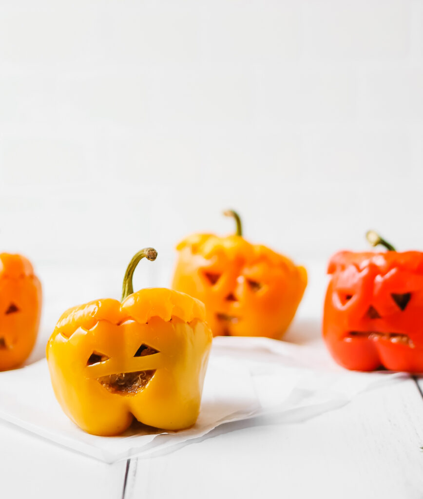 Spooky vegan bell pepper jack o'lanterns smiling at the camera on a white wooden table.