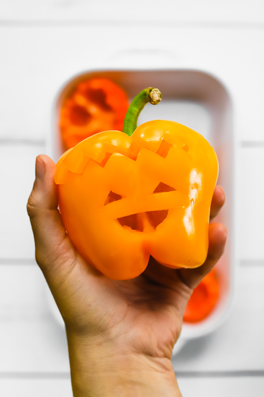 A yellow bell pepper with the happiest spooky little jack o'lantern face carved out of it.