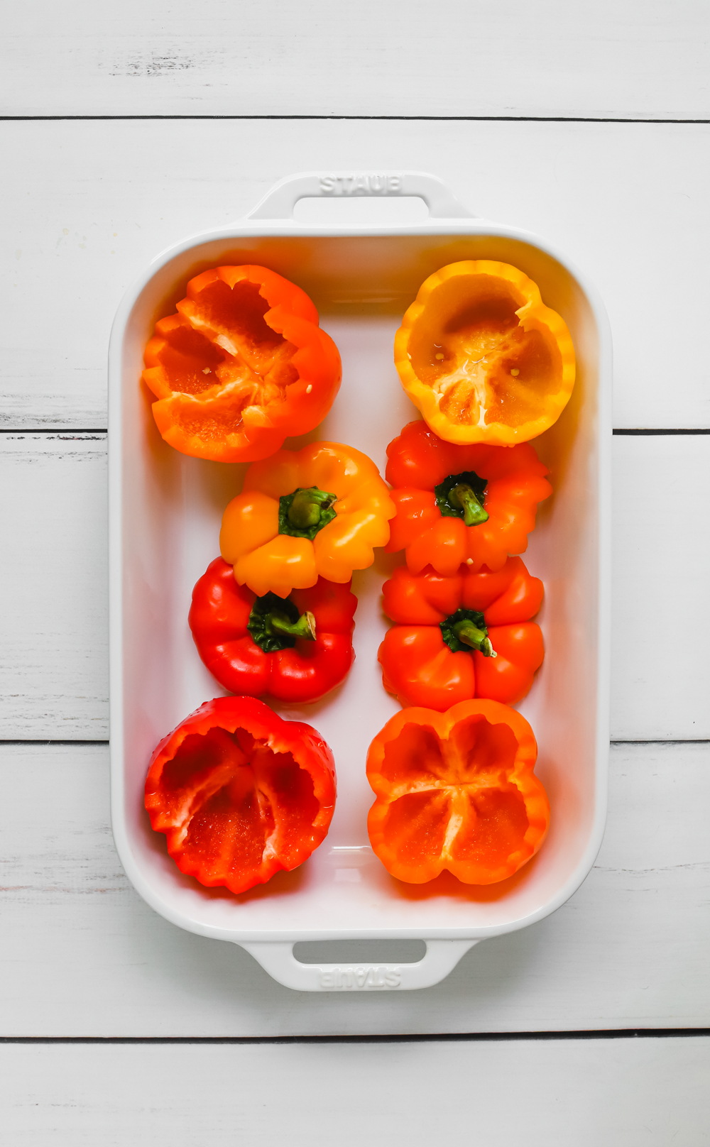Four yellow, orange, and red bell peppers and their tops in a large white high rimmed baking dish.