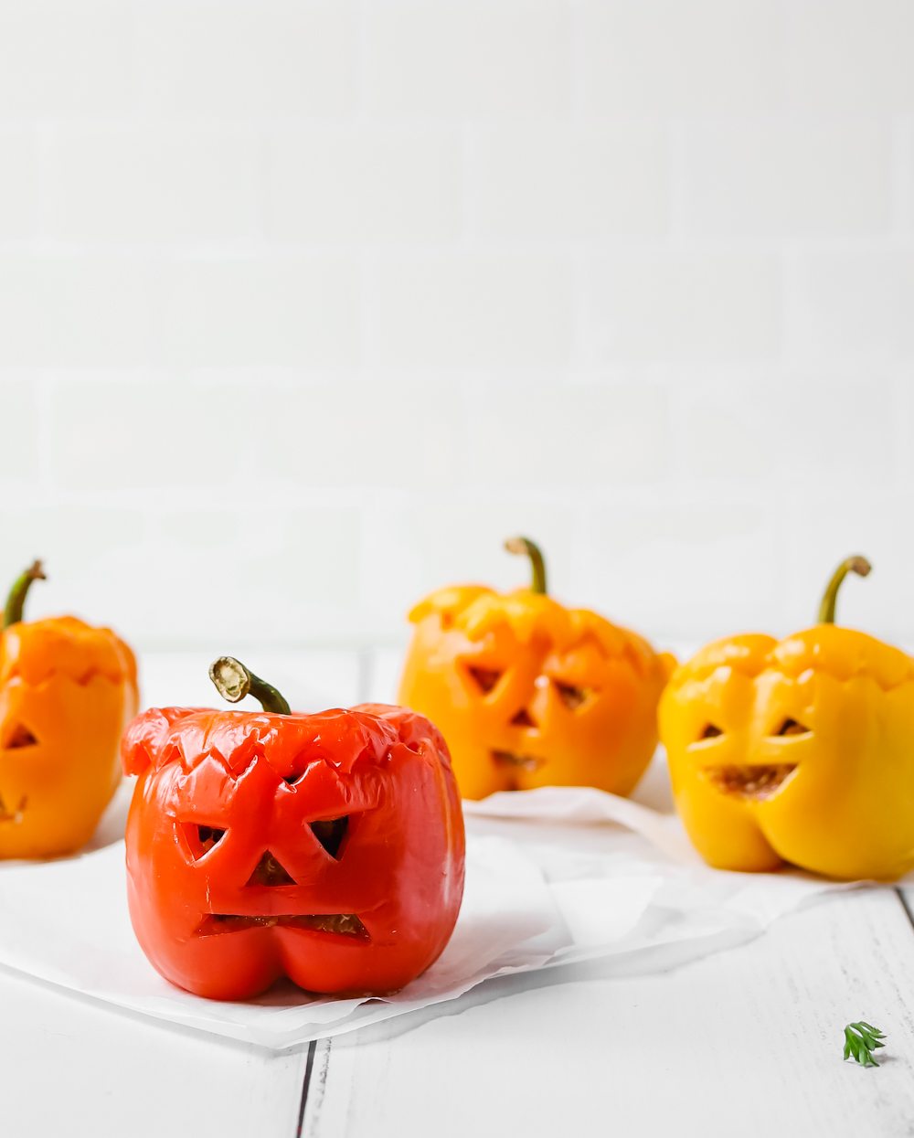 Spooky vegan bell pepper jack o'lanterns on a white wooden table.