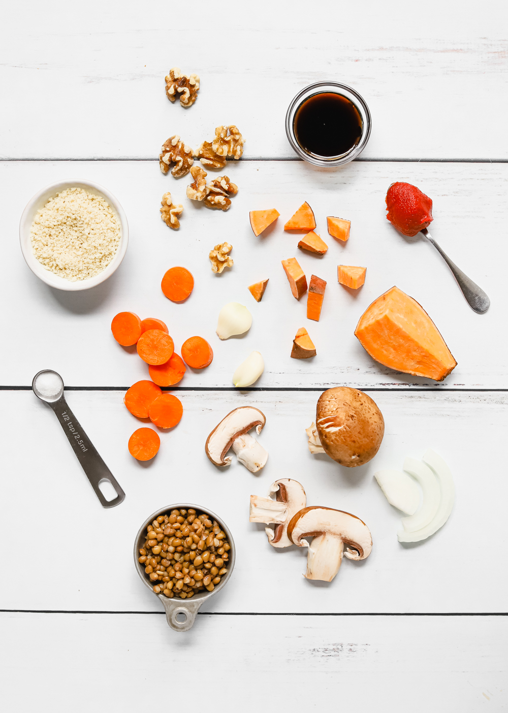 Ingredients to make vegan lentil meatloaf: lentils, mushrooms, sweet potato, carrots, onions, garlic, walnuts, tomato paste, dried thyme, dried rosemary, salt, vegan worcestershire sauce, and breadcrumbs.