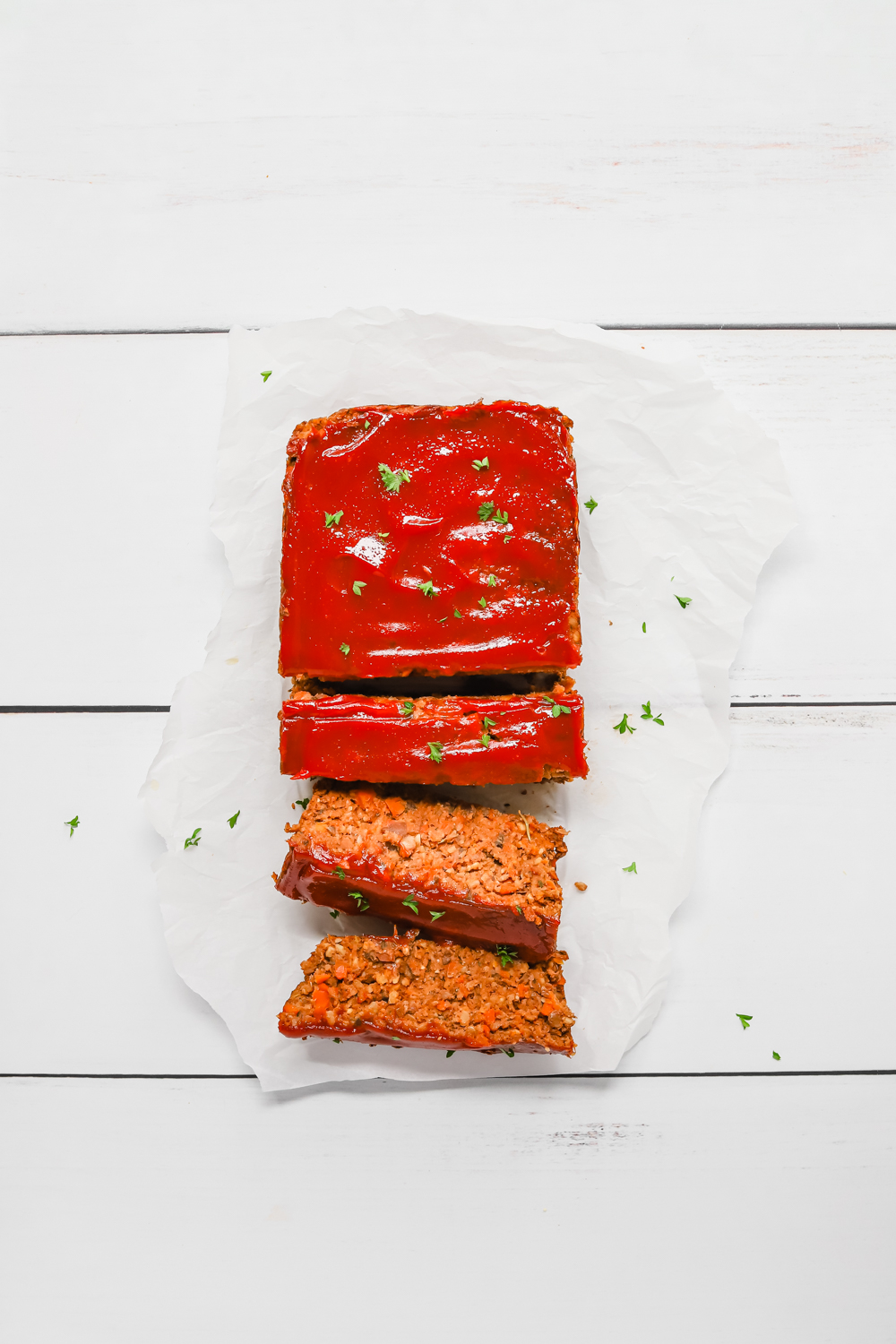Vegan lentil meatloaf with ketchup glazed sliced into pieces and sitting on white parchment paper.