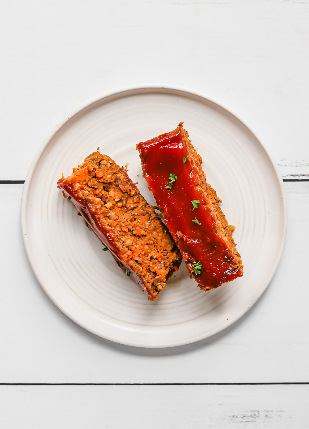 Two slices of vegan lentil meatloaf on a white place topped with a little bit of parsley.