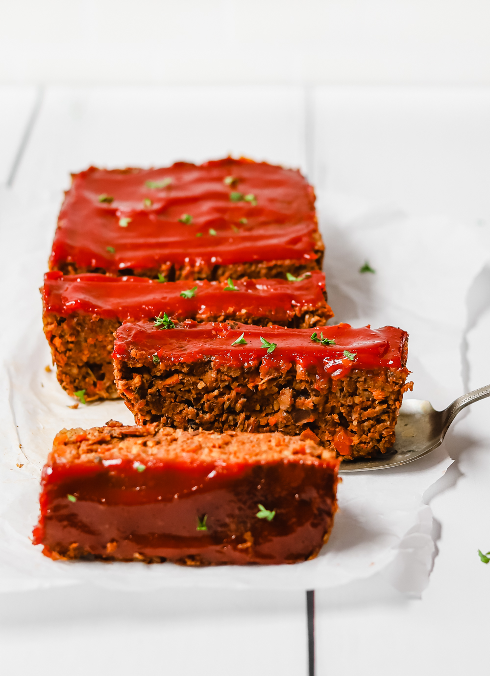 Vegan meatloaf with ketchup glazed sliced into pieces and sitting on white parchment paper.