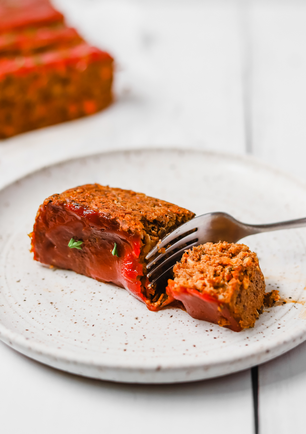 A piece of vegan lentil loaf being cut with a fork.