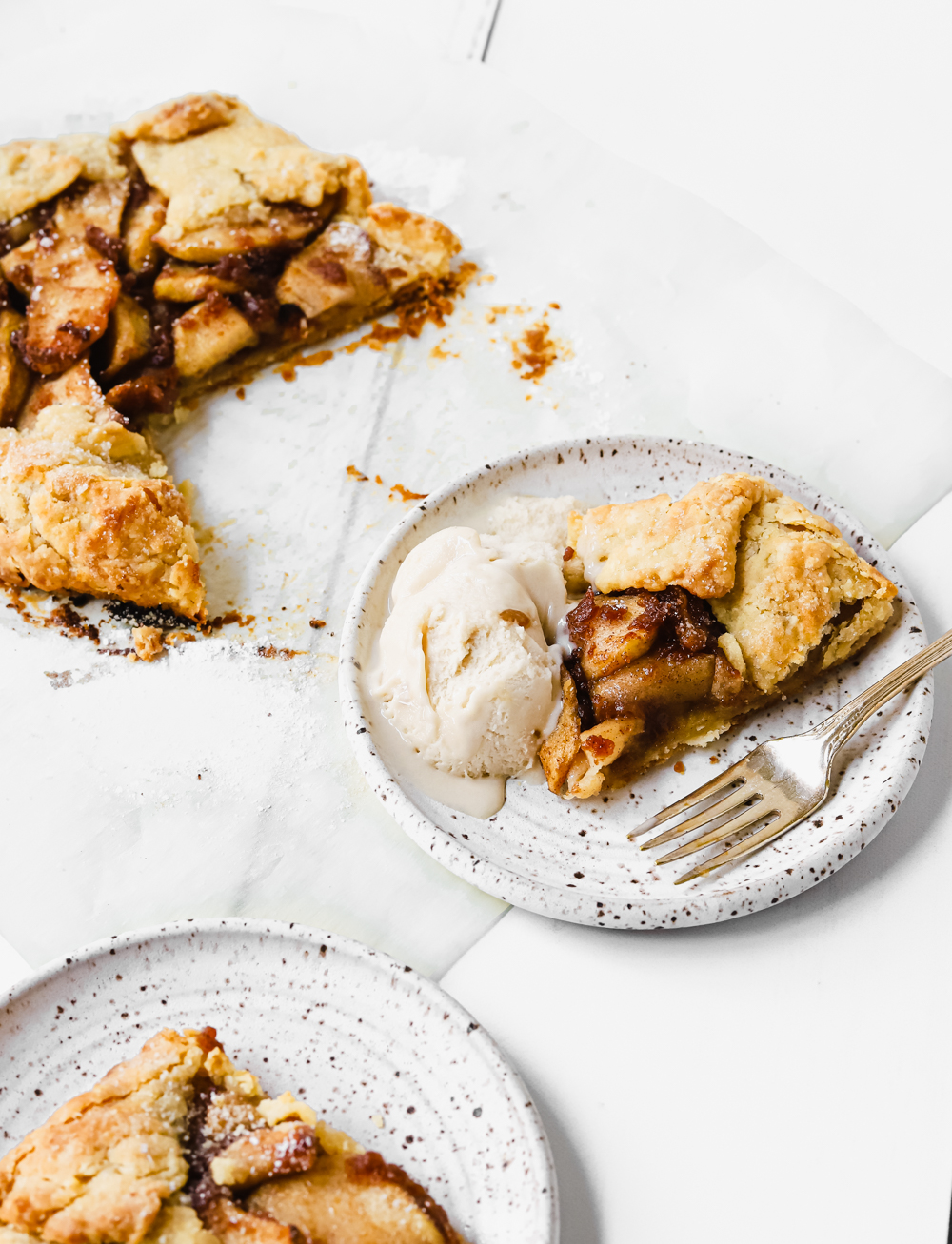 A slice of vegan apple pie galette on a small white speckled plate with a fork and scoop of vanilla caramel ice cream.