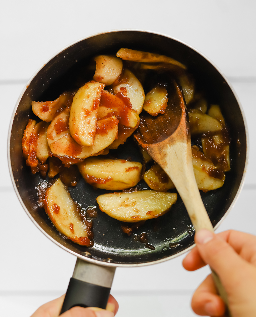 A small pot full of cooked apples coated in a cinnamon, sugar, butter, and cornstarch mixture.