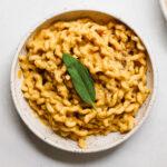Big bowl of vegan pumpkin miso pasta with a fresh sage leaf.