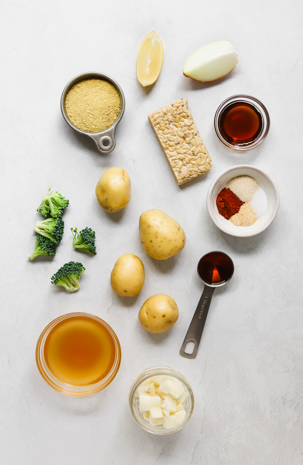 Ingredients to make a vegan potato broccoli casserole with tempeh sausage crumbles: potatoes, diced potatoes, broccoli, tempeh, vegetable broth, maple syrup, liquid smoke, onion, lemon juice, and spices.