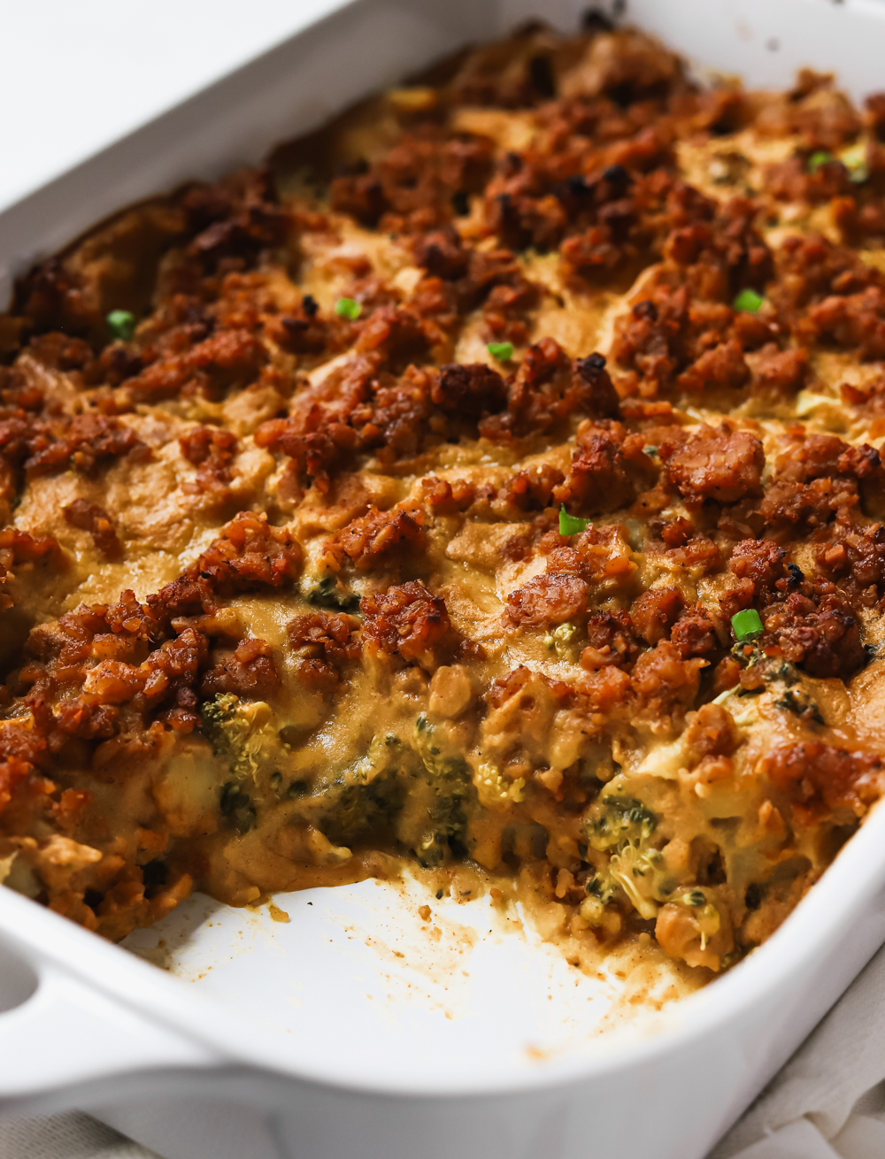 Cheesy vegan broccoli potato casserole with tempeh sausage crumbles with a big scoop taken out of it.