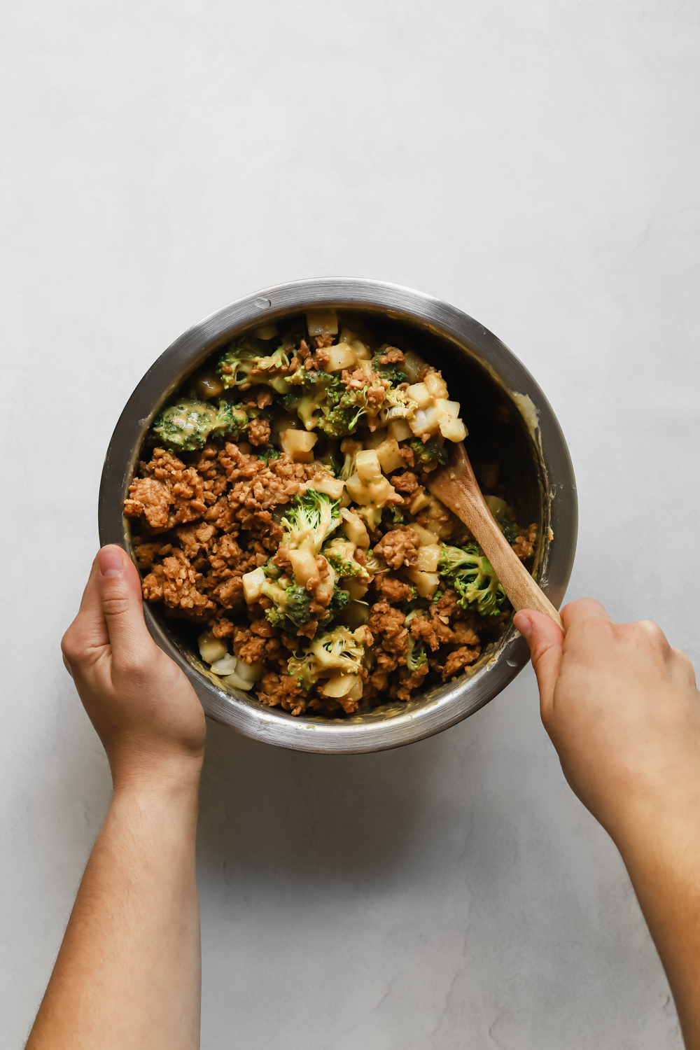 Mixing together diced potatoes, broccoli, tempeh sausage crumbles, and vegan potato cheese sauce in a large mixing bowl.
