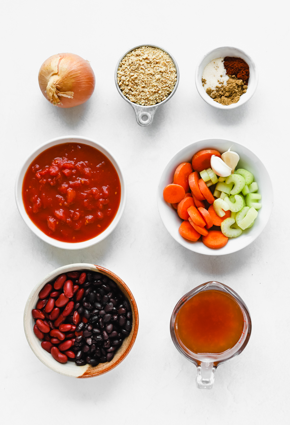 Ingredients to make meaty vegan TVP chili: kidney beans, black beans, textured vegetable protein, carrots, celery, vegetable broth, crushed red tomatoes, onion, garlic, onion powder, chili powder, and cumin powder.