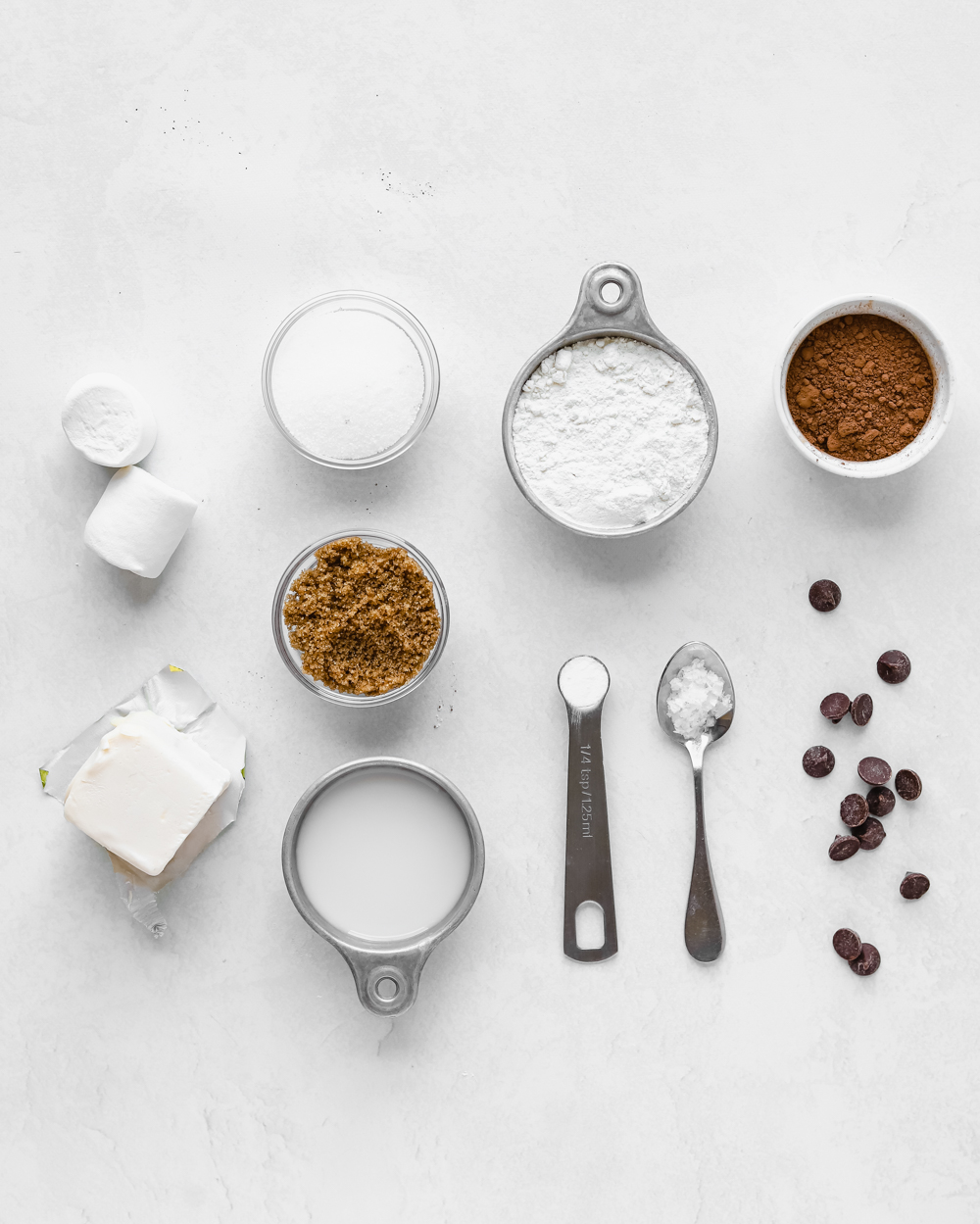 Ingredients to make vegan hot chocolate cookies: butter, brown sugar, white sugar, cocoa powder, flour, almond milk, marshmallows, chocolate chips, salt, and baking soda.