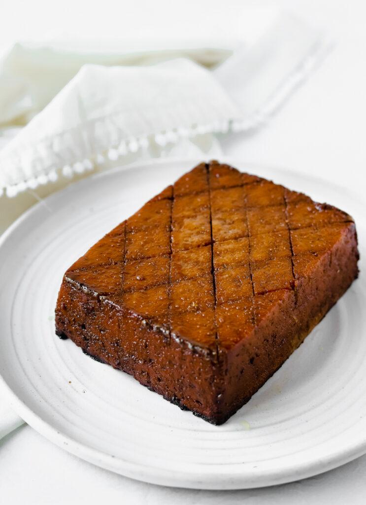 "Vegan orange glazed tofu ""ham"" on a white plate."