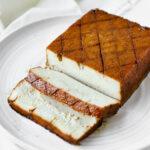 "Sliced vegan orange glazed tofu ""ham"" on a white plate."