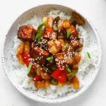 A bowl of sweet and sour tofu over rice and topped with green onions and white sesame seeds.