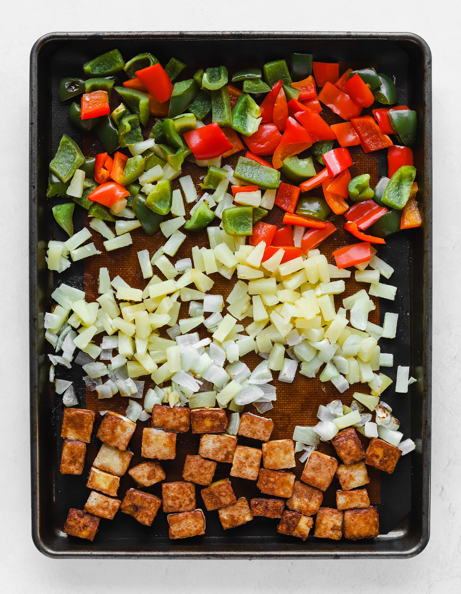 Baked green bell peppers, red bell peppers, diced pineapple, onion, and tofu on a baking sheet.