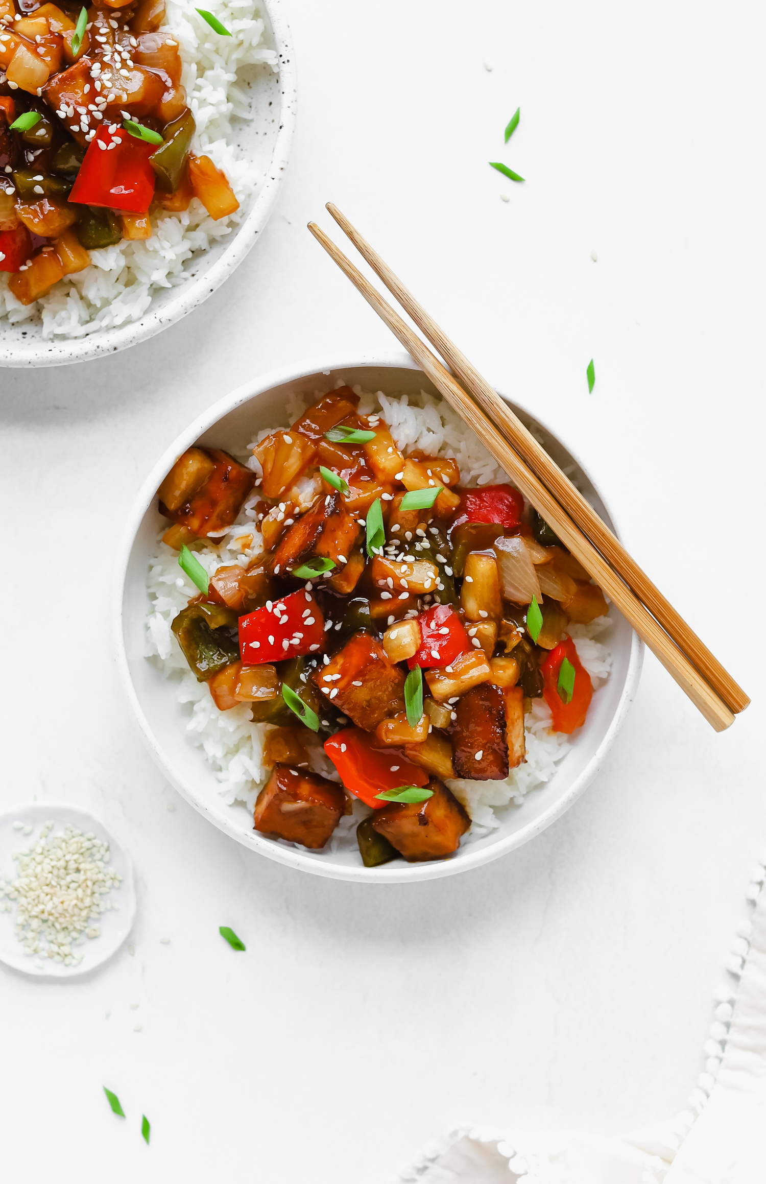 Delicious baked vegan sweet and sour tofu in a bowl topped with green onions and white sesame seeds.