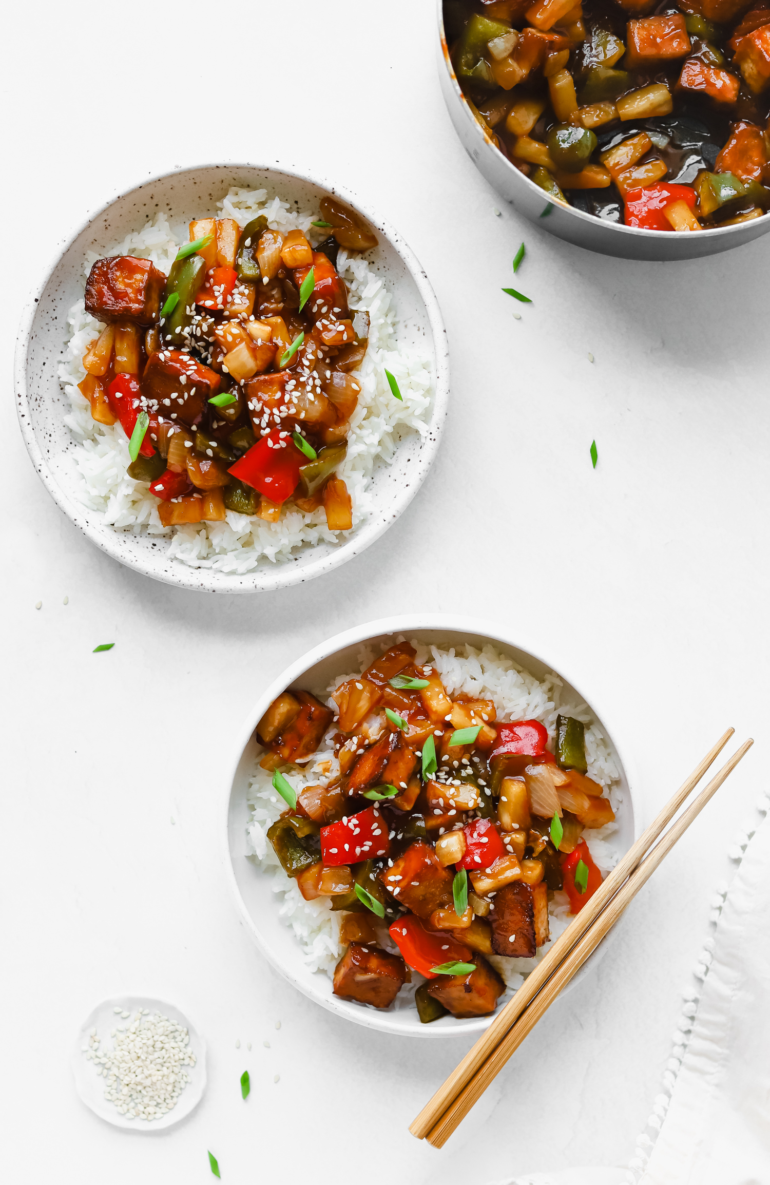 Two bowls of delicious baked tofu topped with green onions and white sesame seeds, smothered with homemade sweet and sour sauce.